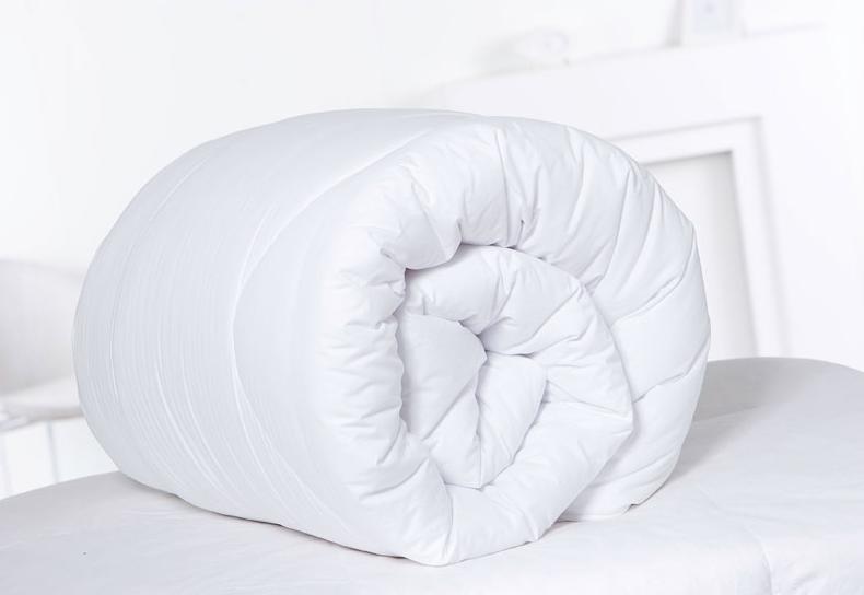 Постиранное и просушенное свернутое пуховое одеяло